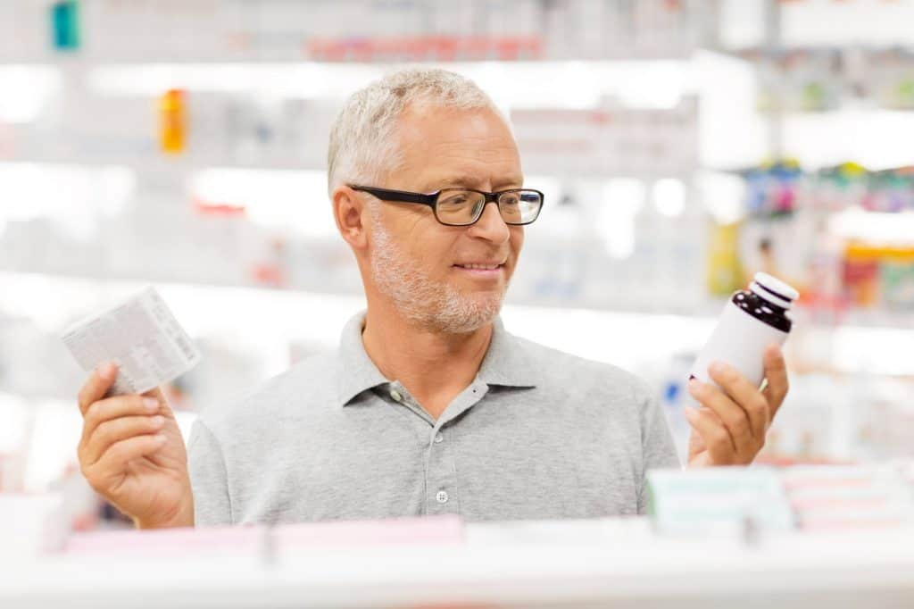 A man looking at labels on medicine.  How to choose the right probiotic.