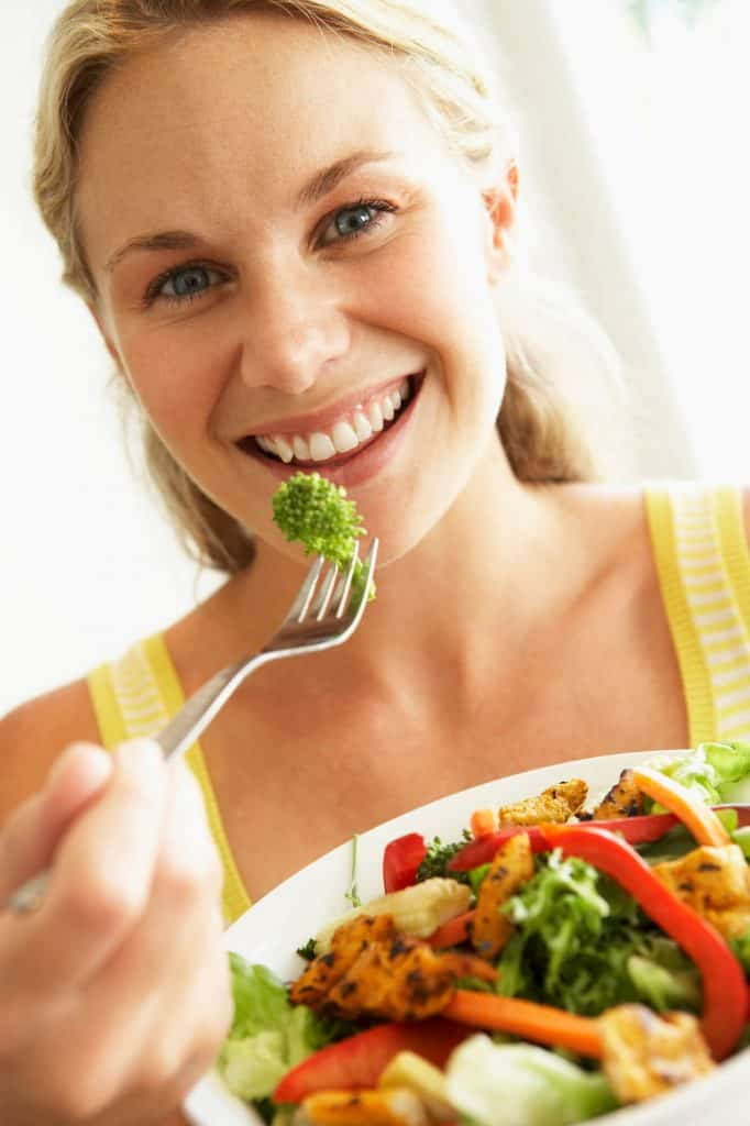 Woman eating a plate of healthy food.