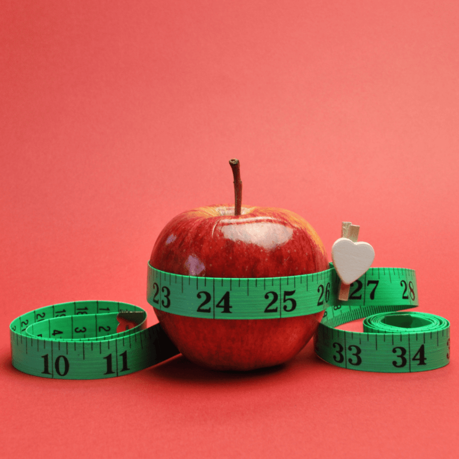 Red background with a red apple and a green tape measure.  Why can't I lose weight?
