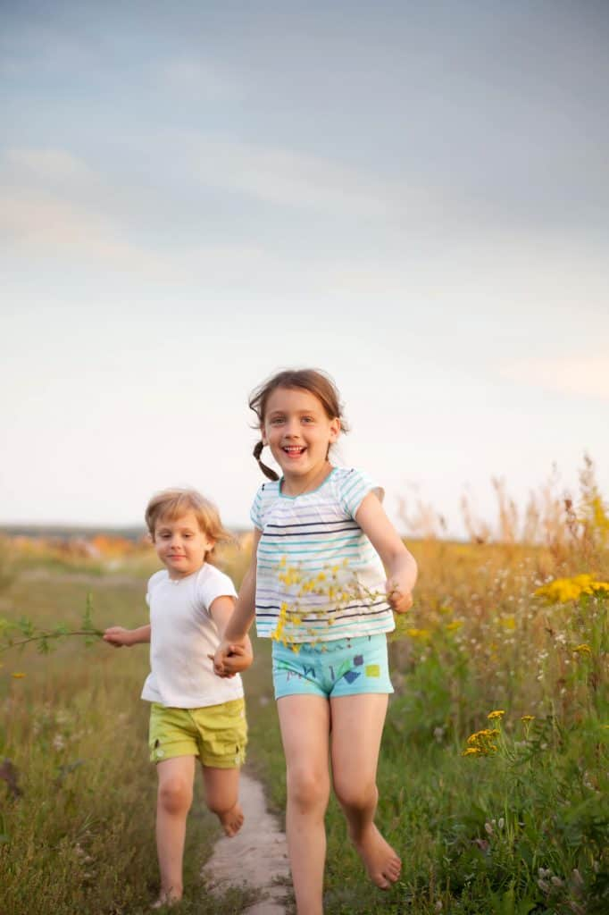 Two barefoot children running