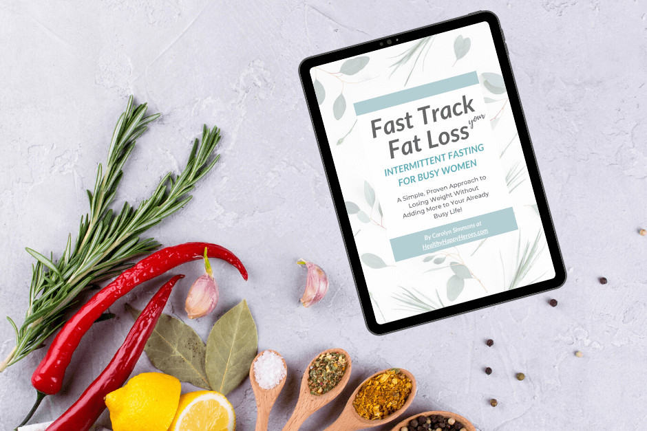 Ipad with intermittent fasting course along with wooden spoons with spices, herbs, lemons on kitchen counter.