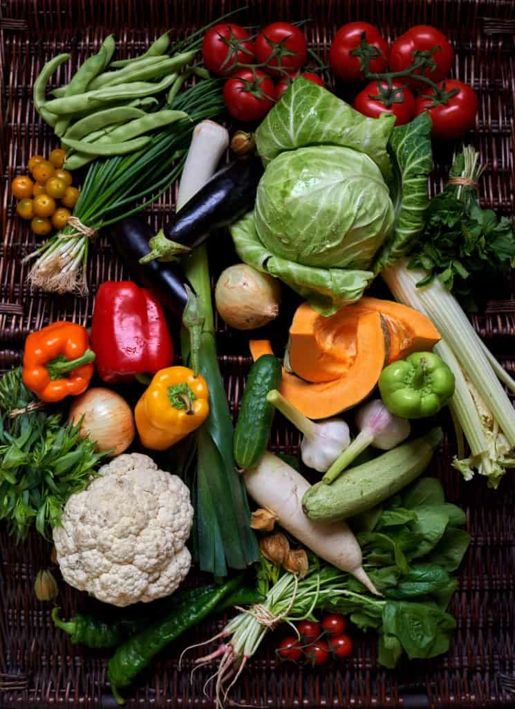 Fresh vegetables on a wicker basket surface.
