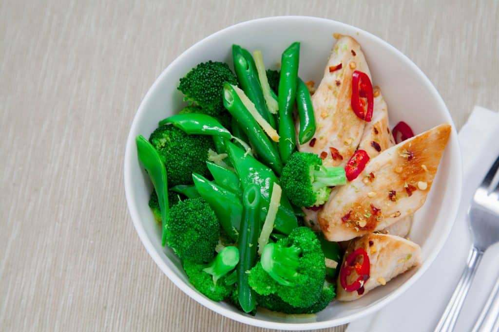 Bowl with grilled chicken with peppers and a mixture of broccoli and green beans.