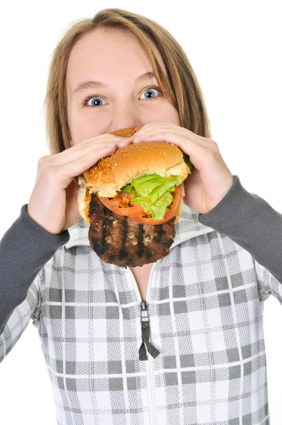 Woman eating a burger.  If you're not losing weight intermittent fasting, check your diet.