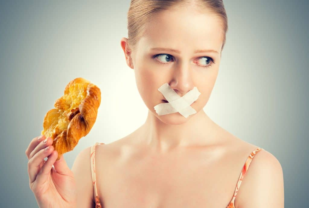 Woman holding a donut with tape across her mouth.