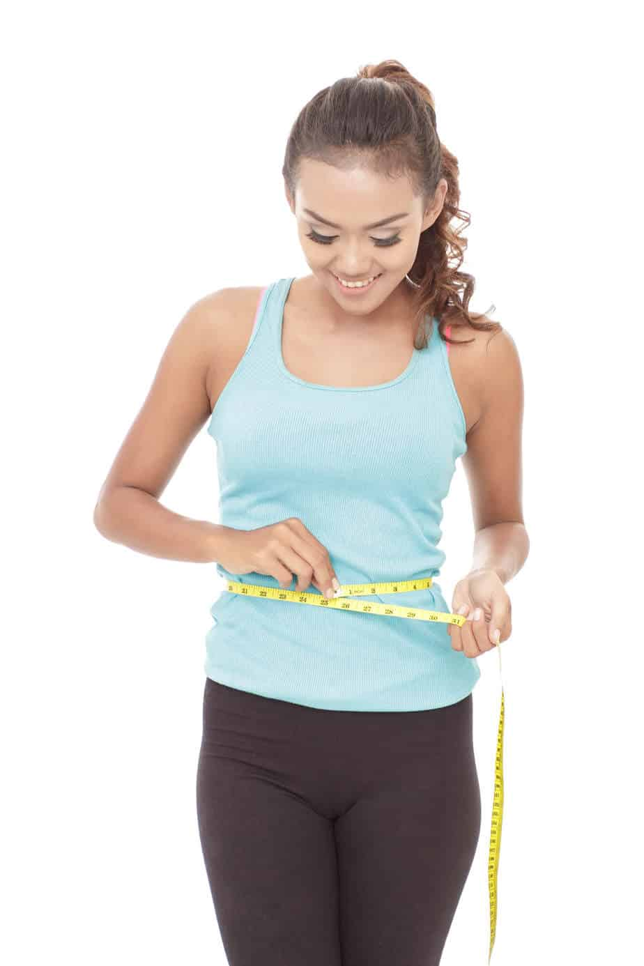 Woman measuring her waist.  If you want to lose weight on intermittent fasting, try different measures of success than just the scale.