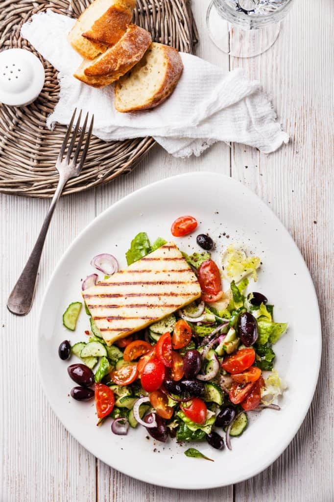 Mediterranean salad and swordfish on a white plate - a good example of a microbiome diet meal.
