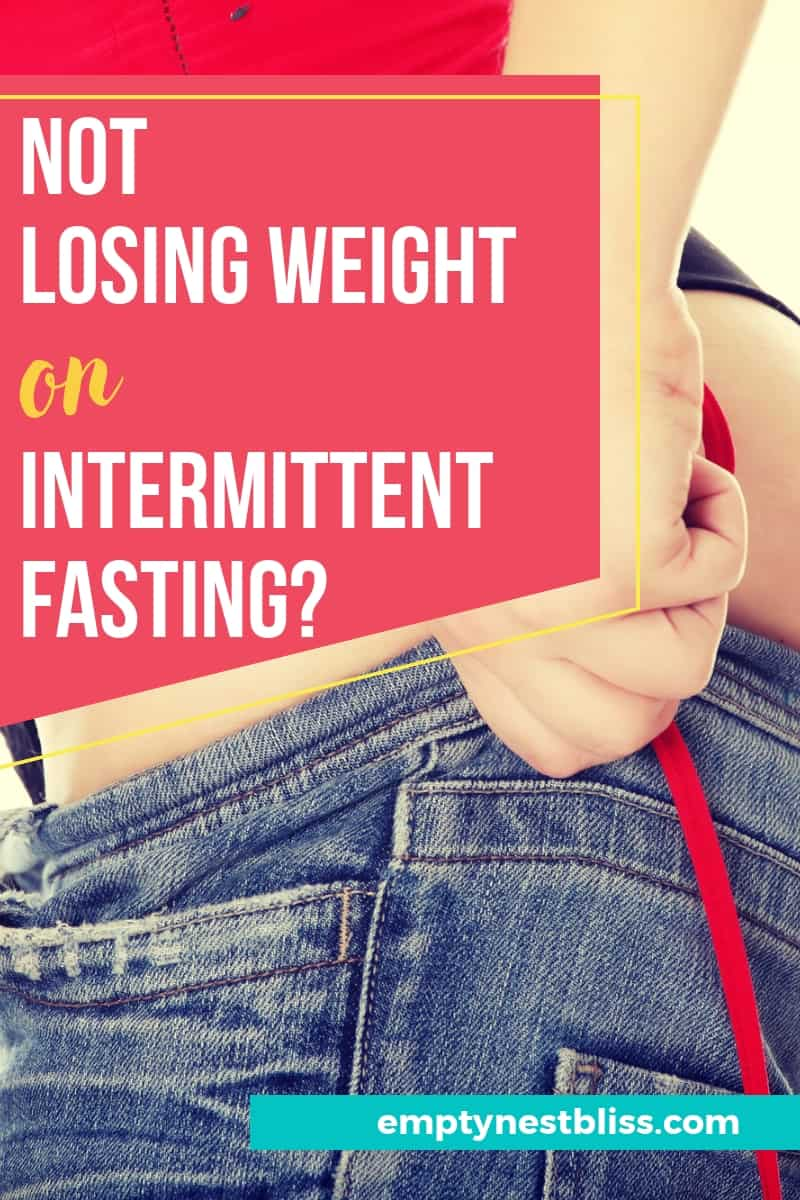Woman trying to pull up her favorite jeans.  Graphic of why are you not losing weight on intermittent fasting.