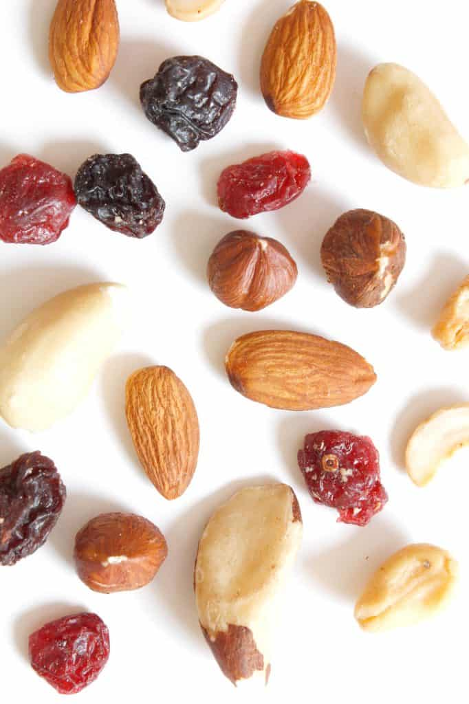 White background with assortment of nuts and dried fruit.  Why can't I lose weight when iIexercise and eat right?