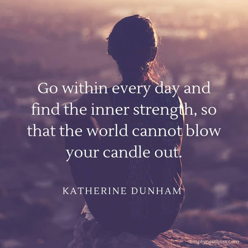 quote:  Go within every day and find inner strength, so that the world cannot blow your candle out.  by Katherine Dunham.  Image showing a woman sitting on a cliff overlooking a city with the sun setting.